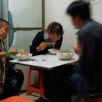 A Chinese family at a restaurant having an evening meal of noodles.