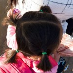 I love the way young Chinese girls often have four pony tails instead of two. Here - a top down view of a girl sitting on the back of her mothers bicycle.