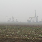 A landscape full of oil pumps that looked like pensioned transformers in the mist.